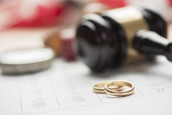 Wedding rings sitting next to a gavel